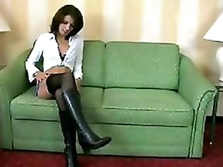 Amateur brunette in  boots and black stockings does a guy on a green couch