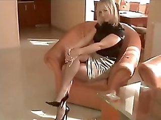 Sexy sexually available mom in blouse and stockings gives a footjob